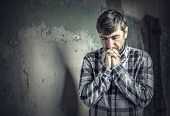 stock photo of praying  - man praying on the background of old wall - JPG
