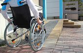stock photo of injury  - Woman in a wheelchair using a ramp - JPG