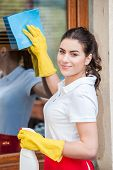stock photo of window washing  - Smiling woman cleaning windows with glass cleaner wearing yellow gloves and red apron - JPG