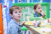 Little handsome boy and girl sit at table and eat in colored room. Focus on boy