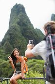 Couple taking photos having fun lifestyle hiking on Hawaii in outdoor activity. Woman and man hiker