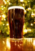 stock photo of guinness  - Celebrating Christmas in Ireland with a pint of black beer over golden lights decorated tree - JPG