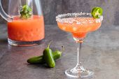 stock photo of jalapeno  - Spicy Hawaiian margarita made by soaking sliced jalapenos in guava juice tequila and grand marnier with pink Hawaiian sea salt - JPG