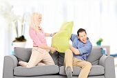 Young couple fighting with pillows indoors