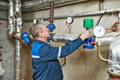 stock photo of manometer  - repairman engineer of fire engineering system or heating system open the valve equipment in a boiler house - JPG
