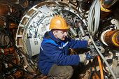 foto of tunnel  - Tunneller sinker worker connecting equipment in tunnel of sewer collector at undergroung working - JPG