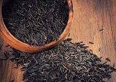 pic of staples  - wild black raw rice in a wooden bowl
