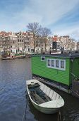 stock photo of houseboats  - amsterdam canal with houseboat and historical houses - JPG