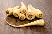 foto of parsnips  - Stack of vegetable parsnips on a wooden table - JPG