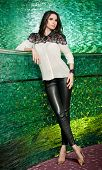 stock photo of black pants  - Attractive brunette woman with long hair in elegant black and white blouse and black leather pants standing near a bar in night club - JPG