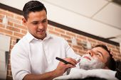 foto of barber razor  - Handsome Latin barber shaving another man - JPG