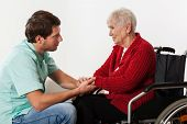 stock photo of compassion  - Young nurse full of compassion assisting lady on wheelchair - JPG