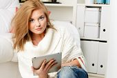 woman sitting in living room and holding tablet