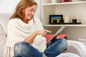 woman sitting on sofa with tablet pc at home
