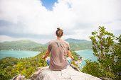 stock photo of samadhi  - Yoga meditation in lotus pose by man on the peak of mountain  - JPG