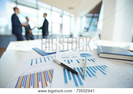 Spreadsheets with charts on office table
