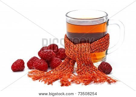 Cup Of Tea In Comforter With Raspberry On White Background