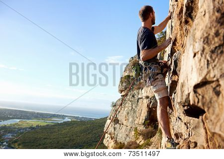 A male rockclimber climbing up a steep mountain attached to a rope and harness looking at the view
