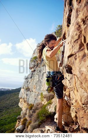 A rockclimbing guy with dreadlocks finding a foothold on a steep mountain