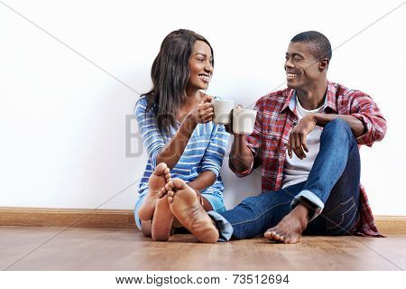 Young african couple sitting on floor of new home with coffee and being happy with life success of property investment