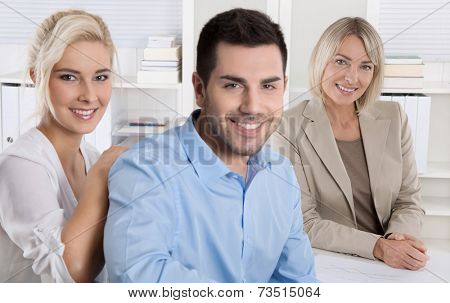 Young smiling couple sitting in a sales conversation at bank or insurance.