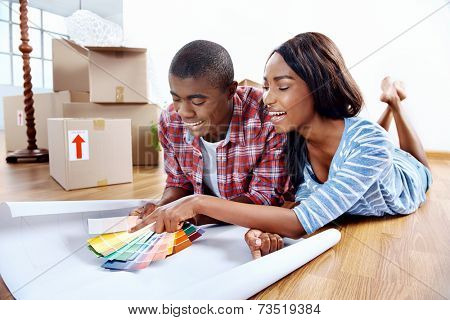 young african couple having fun deciding on paint colour swatch for new home apartment