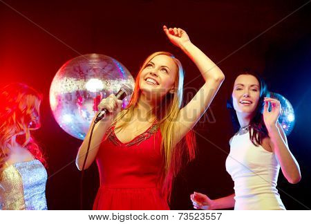 new year, celebration, friends, bachelorette party, birthday concept - three women in evening dresses dancing and singing karaoke