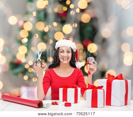 holidays, celebration, decoration and people concept - smiling woman in santa helper hat with scissors packing gift boxes over christmas tree and lights background
