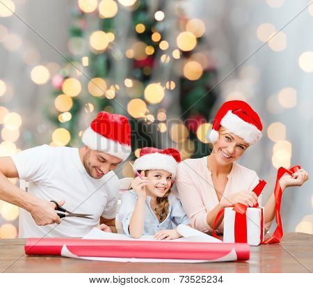holidays, family and people concept - happy mother, father and little girl in santa helper hats with gift box and scissors over christmas tree lights background
