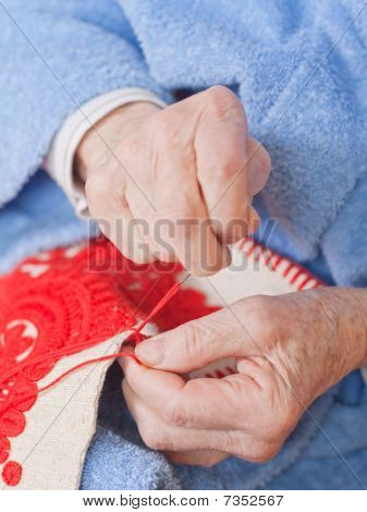 Old Woman Sitting On The Bed, And Sewing Something