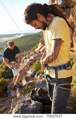 Two men putting on their harness and rock climbing equipment