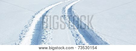 Car tire tracks in snow