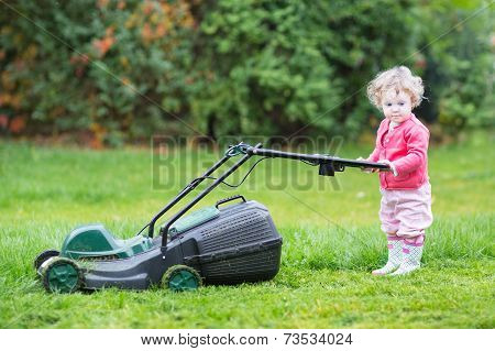 Cute Toddler Girl With A Lawnmower In The Garden