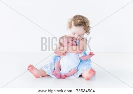Sweet Toddler Girl In A Blue Dress Kissing Her Newborn Baby Brother