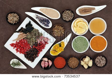 Immune boosting health superfood selection in porcelain dishes and wooden bowls over lokta paper background.
