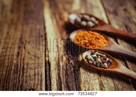 Three wooden spoons with spices, close-up