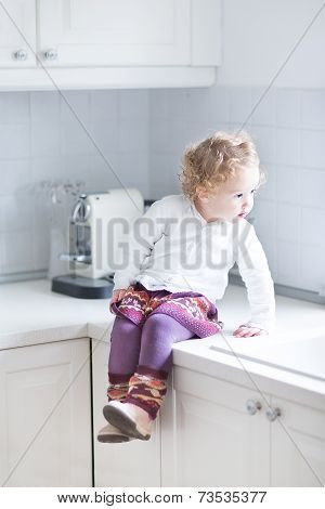 Adorable Toddler Girl Sitting In A White Kitchen On The Countertop Ready For Dinner