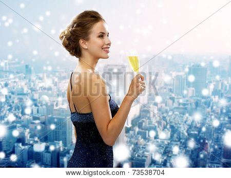 drinks, christmas, holidays and people concept - smiling woman in evening dress with glass of sparkling wine over snowy city background
