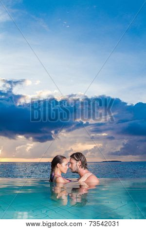 Young couple enjoying a romantic swim standing chest deep in the sea facing each other in an intimate embrace copyspace in the sky