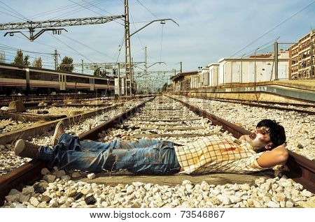 a scary zombie taking a nap at abandoned railroad tracks