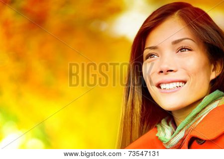 Autumn / Fall woman in colorful foliage in city park forest smiling happy. Portrait of modern girl and colorful leaves outdoor in fall forest foliage. Mixed race Asian Caucasian female model.