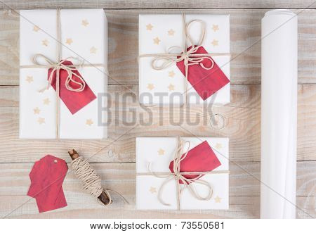 High angle shot of three Christmas presents wrapped in white paper and tied with white string. The gifts are on a white wood table with string, tags and a roll of paper.