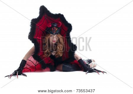 Wary red-haired girl posing in devil costume