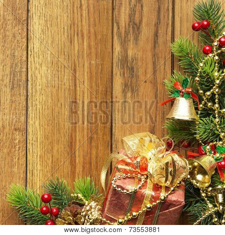 Decorated Christmas tree border on wood paneling with gold baubles and bells, a decorative Xmas gift wrapped in a golden bow, holly and beads with copyspace for your seasonal greeting