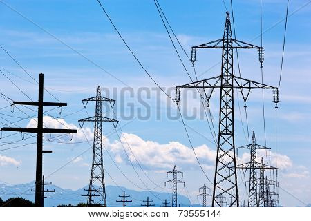 a high voltage pylons for electricity against blue sky.