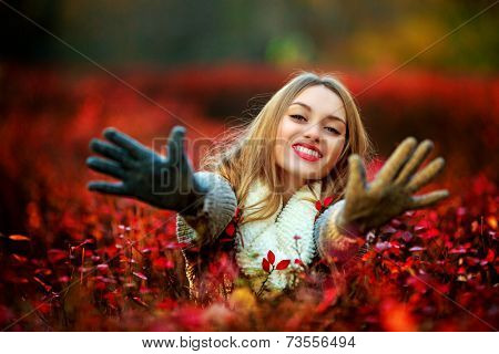 happy young woman in the autumn park, stretching hands to us