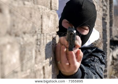 Criminal Targeting Into The Camera With A Gun