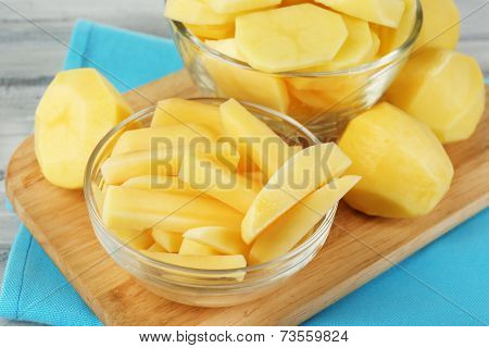 Raw peeled and sliced potatoes in glass bowls, on cutting board,  on color wooden background