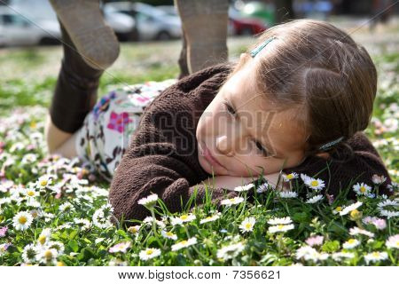 Girl lying in field of daisies