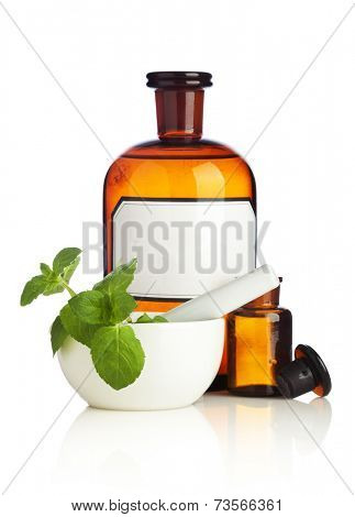 Pharmacy bottles, mortar and herbs on white background